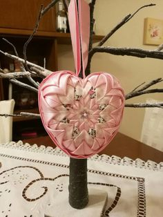Beautiful quilted heart ornament to accentuate your home decor. I crafted this heart with the utmost love and care and great attention to detail in a smoke free / pet free environment, using three different fabrics. Quilted with pink satin combined with plaid cotton fabric and light floral cotton. Notice the little pink flower embellishments! Size: Folded fabric on a Styrofoam 11cm heart (4.33 inches). This fabric heart would be a beautiful door hanger and a perfect addition to your lit...
