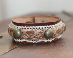 Custom leather cuff bracelet, made out of quality leather, lace, Antique Brass hardware and Brown Braided Fabric. Over all length 7 1/2.