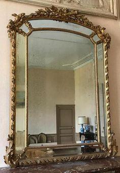 Important miroir à parecloses en bois et stuc doré, le sommet décoré