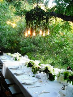 Custom chandelier at an outdoor wedding blends in with the rustic canyon landscape and hangs over two beautifully decorated long tables