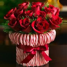 Stretch a rubber band around a cylindrical vase, then stick in candy canes until you cant see the vase. Tie a silky red ribbon to hide the rubber band. Fill with red and white roses or carnations.