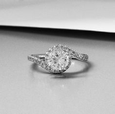 In this glamorous and whimsical ring, fluid curves of scalloped pavé diamonds encircle the center diamond.
