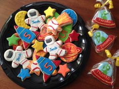 Space themed sugar cookies with royal icing.  Spaceman cookies as favors. Astronauts, stars, planets, rockets. Bday boy loves baseball so there were also baseball comets.