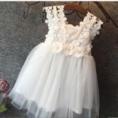 Pearls, delicate floral trim, and a tulle skirt. This dress has it all!  Size (cm) 18-24m 2T 3T 4T 5T Chest 25.5 26 27.5 28 30 Length 46 47 51 54 58