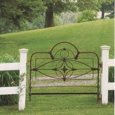 Great simple idea from http://www.curioussofa.com. Now that's using what you've got to dress up your fence. An old iron headboard.