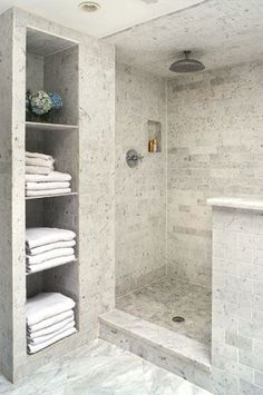 Great use of space in a Bathroom Love the walk in Waterfall Shower the tile work and a Cubby for the Towels Awesome Concept