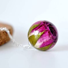 Artist Paula Schiau (of Resity) crafts jewelry that looks as though it belongs in a fairy tale. Using handpicked, dried flower buds evoking a sense of romance, the designer encapsulates these natural creations in polished resin or in delicate glass vials that hang from various chains. Perhaps the most unique aspect of Schiau's work is that the flowers will never wither or die, since they're preserved forever in her unique, handmade pieces. As of right now, Schiau is an art student who makes…