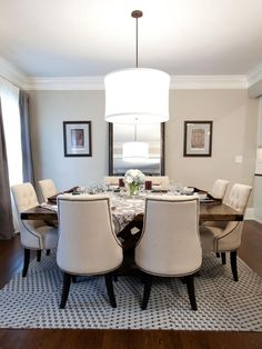 AFTER: The room looks infinitely larger with a neutral off-white paint color. An over-sized fabric chandelier centers the room as it hangs over a large table with studded fabric chairs.