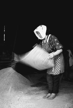 "From the exhibition"" Family of Man"" -- Working the rice grain. By Ihei Kimura"