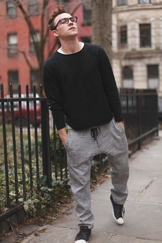 Grey Sweatpants styled with Black Full Sleeves Tshirt and a pair of Black Sneakers gives a relaxed look