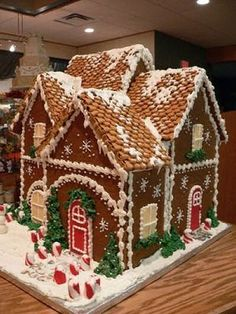 Great detail on the roof of this pretty gingerbread house and I love the candy cane posts.