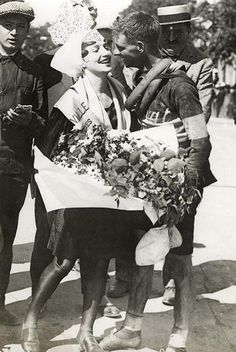 """Tour de France 1928. The podium girls didn't seem to have had podiums back then. """"Kisses and flowers from the local beauty for Hubert Opperman, after the 6th stage (Vannes-Les Sables d'Olonne, 204 km). France, Sables"""" Source: http://www.flickr.com/photos/nationaalarchief/3675431958/in/set-72157620769456464"""