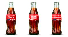 """Through July 31, fans can visit ShareaCoke.com to buy customizable """"Share an ICE COLD Coke"""" bottles with a design inspired by the American flag and the USO logo."""
