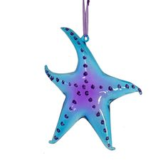"""Add a pop of color to your decor with this glass starfish ornament. Featuring vivid and bright tones of cool blue and purple, this glass ornament is bound to catch the eye. Perfect as a gift, memento, or Christmas tree ornament.  Dimensions: 5.5 x 5.5""""  Item: #10862 $10.95"""