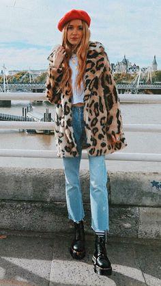 10 formas estilosas de usar pelinhos no inverno. Boina vermelha, casaco de pele fake com estampa de animal print, cropped branco, calça jeans, coturno preto