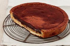 Tritate finemente il cioccolato, riunitelo in una ciotola resistente al calore con la panna, scioglietelo a bagnomaria, mescolate, unite il burro a dadini e...