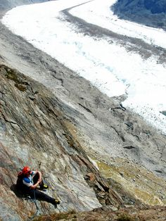 A climber taking a break during a multi pitch rock climbing route on the Riffelhorn, Swiss Alps.