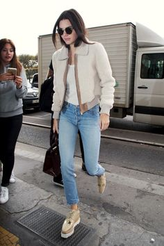 Kendall Jenner wears a shearling jacket, jeans and Stella McCartney platform oxfords.