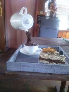 Zwevende koffiepot met taartje. Nodig: koffiepot,kop en schotel en theelepel, eetlepel met een smalle eind, lijm, koffiebonen, taartje is gemaakt van stukje oase, diverse soorten hout snippers, sinaasappel schijfjes, en hout rondjes.