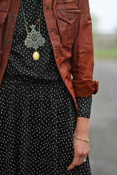 Love the mix of texture and pattern with the fine print dress and leather jacket. And a statement necklace!