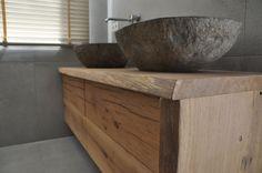 Oud eiken badmeubel met , bovenblad en zijkant van een eiken boomstam en de wastafels van riviersteen.