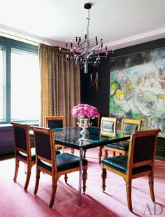 Frédéric Malle's dining room features a Roberto Matta painting to temper the starkness of the black walls. The space has a glass dining table, wood and leather chairs, pink carpets, floor to ceiling curtains and a ultra-modern hanging light fixture.