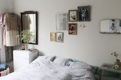 visible clothing, frame placement, photos and frames add color, neutral bedding