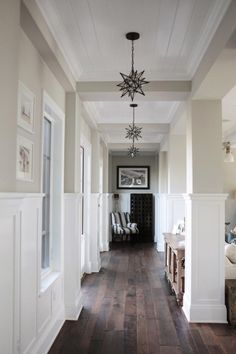 Don't be afraid to use only one light fixture as the focal point of your entryway. Consider using multiple light fixtures, such as the Star pendants in this home, that can be seen down the long hallway from the front door.