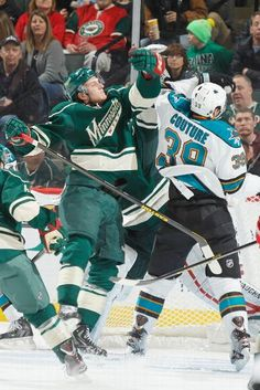 Jonas Brodin of the Wild and Logan Couture of the Sharks battle for control of an airborne puck  3-23-13