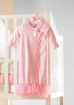 This luxe soft pink velour sleeper is trimmed with ruffles and a satin bow and features an easy snap front closure. Makes the perfect baby shower gift. Fits size 0-6 months. Part of Mud Pie's Pretty in Pink collection. It's pink perfection! Girly glamour gets her attention in the Mud Pie Pretty in Pink collection, with all the frills and thrills that little girls adore.