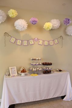 Lavender and yellow baby shower decor. Invitations, favors, banner, paper pom poms and more.
