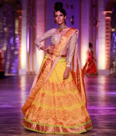 Neeta Lulla yellow net lehenga with orange kanjivaram appliqué and a gold kanjivaram border with green trim at the hemline. The lehenga is worn with a full sleeved nude blouse and a white net dupatta with gold kanjivaram borders. Banarasi Lehenga, Lengha Choli, Net Lehenga, Bridal Lehenga, Indian Dresses, Indian Outfits, Indian Clothes, Western Outfits, Indian Bridal Wear