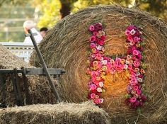 """Bale of hay embellished with the initial """"H"""" in fresh flowers.  Featured on Episode 5, Season One of Bama Glama on Food Network.  Created and designed by Celebrity Event Designer Scot Wedgeworth for the wedding of Lindsey Belcher Hogue in Centreville, Alabama.  www.scotwedgeworth.com"""