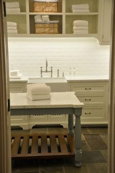 love this. especially subway tiles and under shelves/cabnet lighting for nighttime folding. and island table with storage below