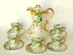"Bohemian Thun porcelain set of Art Nouveau Vienna China: Coffee or Chocolate Pot w/ 5 Demitasse Cups & Saucers lavishly hand painted in pale white blossoms against an aqua, peach, and sky blue background. Made from 1890 -1913 and signed ""Heinz"" by the artist."