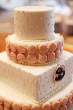 Chic wedding cake adorned with pink macaroons and white sugar pearls.