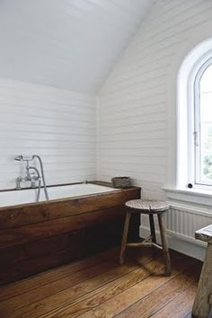 White walls with a dark wood tub surround and floors.