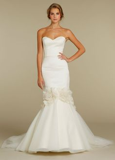 Strapless sweetheart neckline mermaid bridal gown. Delicate jeweled trim at natural waist with tulle skirt emerging from a blossoming jeweled fabric detail.