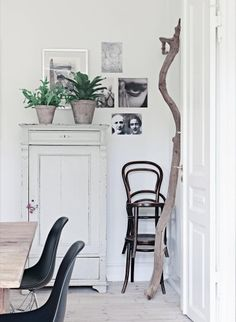 A bohemian home with whimsical art:  The light gray cabinet is a gift from Lotte's mother, who bought it in Jutland. Upstairs find a few pots of plants that provide fun atmosphere. On the wall hangs black and white pictures inspiration from Lotte travels. In the corner beside the cupboard is Thonet chairs, stacked and ready for guests.