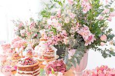 Decoração romântica com arranjos assimétricos em tons de rosa. Doces e bolos em boleiras de porcelana. Decoração: Gláu Miranda