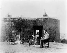 Man sitting in a chair in front of his sod house. SOD HOUSE 1886 NEBRASKA