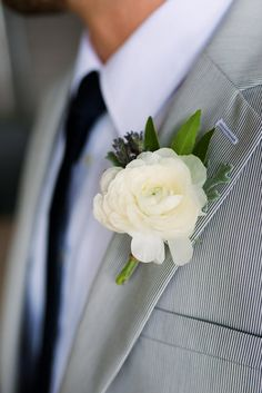 White ranunculus boutonniere - groom in black and white pinstripe suit.