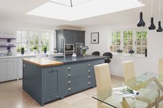 A Grand Design in Malmesbury - Sustainable Kitchens. The centre island with it's dual material Welsh Slate and Oak worktop really is the piece-de-resistance of this design. Not to mention the enormous tap flowing over the top of the elegant undermounted sink, this island steals all the attention.