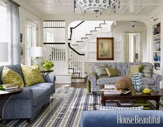 This living room in a Southampton house designed by Marshall Watson, evokes a traditional mid-20th-century American sensibility but with a modern twist. Watson's senior designer, Wendy Monette, mixed colors, patterns, and styles that lend a clean, graphic edge to the room, like the sofa's superscaled houndstooth and the rug's green and navy stripes.   - HouseBeautiful.com