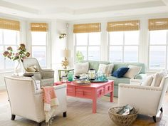 """In the family room of this Massachusetts home, a melon-colored coffee table by Seabrook Classics pops against neutral Lee Industries chairs. The faux-coral table lamp is from Pier and the walls are painted """"White Dove"""" by Benjamin Moore. Cottage Living Rooms, Home Living Room, Living Room Designs, Living Room Decor, Living Spaces, Coastal Living, Country Living, Coastal Style, Coastal Decor"""