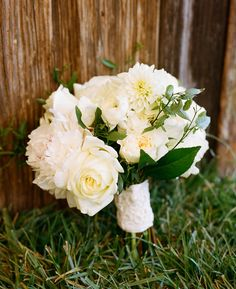Bouquet of blush pink and white peonies, white anemones, white ranunculus, white garden roses, and white hellebores.