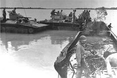 The crews of amphibian tractors board a severely damaged Japanese landing craft which was intercepted by U.S. naval patrols when it carried troops attempting to infiltrate northern Peleliu and reinforce Ngesebus Island off northwest Peleliu.