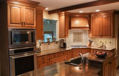 Traditional Kitchen- Stainless steel appliances, table style seating at counter height, recessed corner cooktop with wall ovens, custom wood hood, custom tile backsplash, birch cabinets with granite countertop