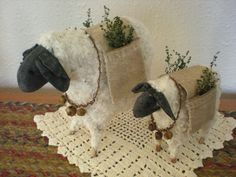 Made from muslin and covered in old cotton batting. Wooden doweled legs. Rusty wire is fashioned around their necks with added rusty bells. Small packs made from aged drop cloth are attached to their backsides with preserved sweet Annie sprigs inside.