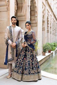 On him - A moon grey raw silk sherwani worn with a tassar silk shawl On her - Our mood blue resham &… Couple Wedding Dress, Wedding Dresses Men Indian, Indian Bridal Outfits, Indian Bridal Fashion, Indian Bridal Wear, Pakistani Bridal, Indian Dresses, Punjabi Wedding, Bollywood Wedding
